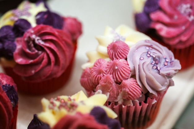 Cupcakes coloridos saborosos com morangos e creme.