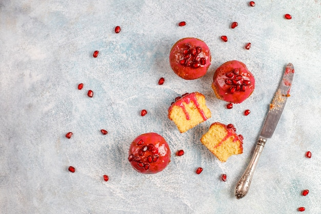 Cupcakes com cobertura e sementes de romã.