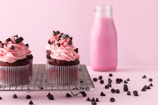 Cupcakes com cobertura rosa e bebida rosa