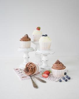 Cupcakes com creme de chocolate e baunilha em mini carrinhos de madeira branco sobre fundo branco