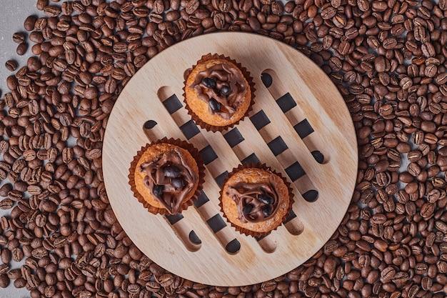 Cupcakes com creme de chocolate na travessa de madeira.