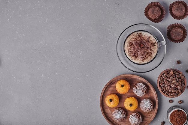 Cupcakes com creme de chocolate servidos com uma xícara de café, vista de cima.