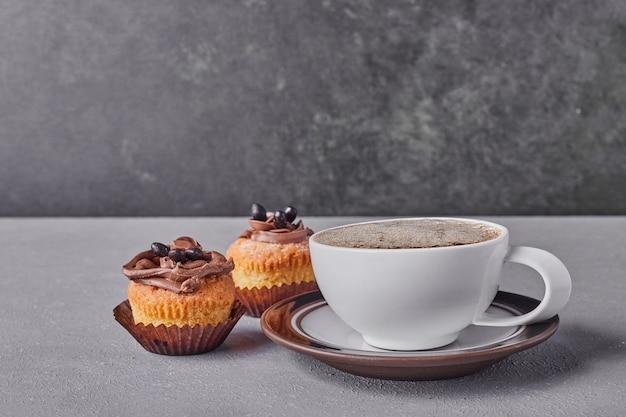 Cupcakes com creme de chocolate servidos com uma xícara de café.