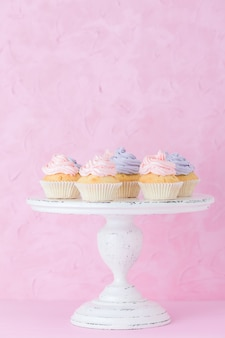 Cupcakes com creme-de-rosa e violeta no branco gasto shec stand em fundo rosa pastel