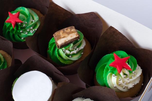 Cupcakes com creme e estrelas vermelhas em um fundo branco.