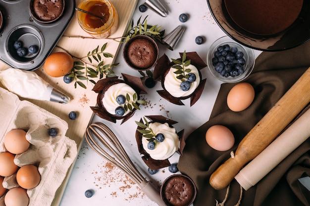 Cupcakes com creme e mirtilos na mesa da cozinha