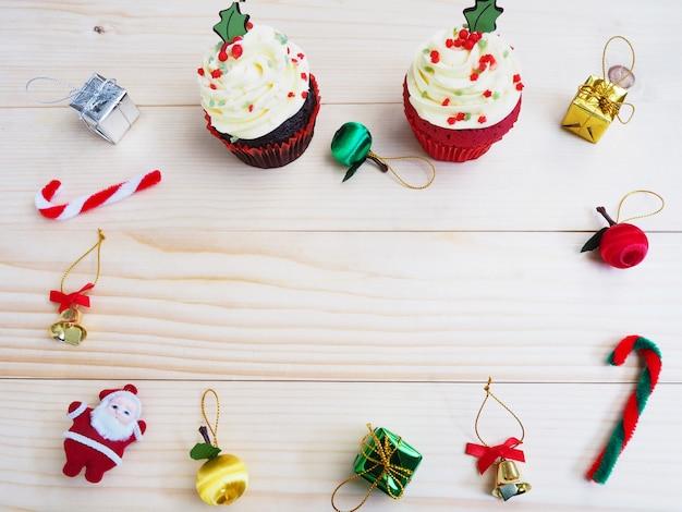 Cupcakes com decoração de forma e ornamento de natal na mesa de madeira