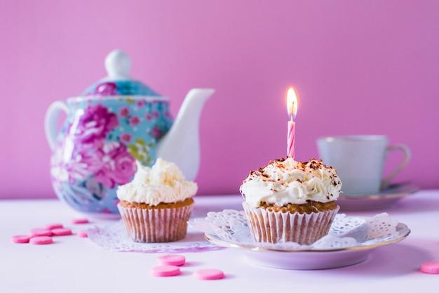 Cupcakes com vela iluminada em cima da mesa