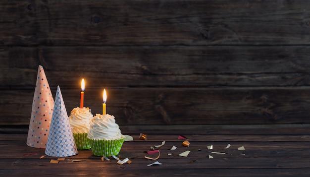 Cupcakes de aniversário com velas na superfície de madeira escura antiga