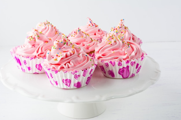 Cupcakes de aniversário rosa decorados no suporte do bolo