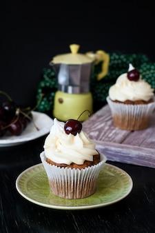 Cupcakes de baunilha com cerejas, um prato de frutas e uma cafeteira