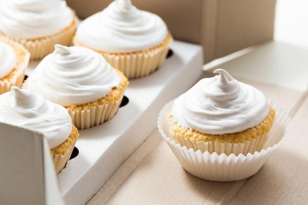 Cupcakes de baunilha com creme branco em caixa de entrega