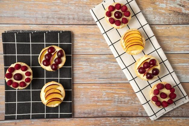 Cupcakes de baunilha com frutas vermelhas do verão na toalha preta e branca
