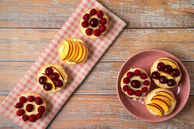 Cupcakes de baunilha com frutas vermelhas do verão na toalha rosa