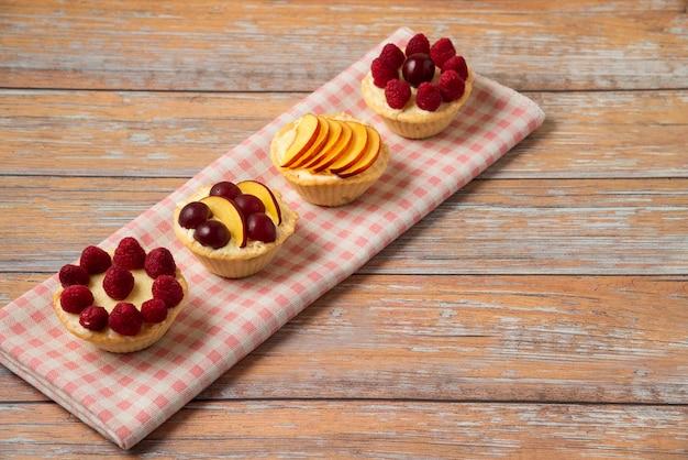 Cupcakes de baunilha com frutas vermelhas na toalha rosa.