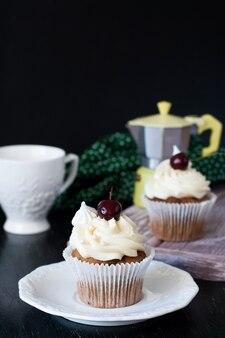 Cupcakes de baunilha e chocolate com cerejas, xícara e cafeteira.