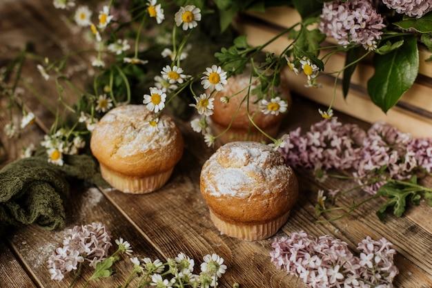 Cupcakes de baunilha sentam-se em uma mesa de madeira entre ramos lilás e flores de camomila.