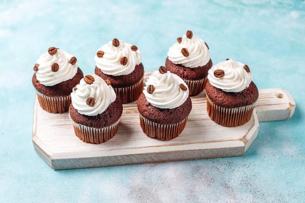 Cupcakes de café decorados com chantilly e grãos de café.