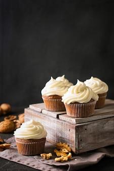 Cupcakes de cenoura ou muffins com nozes em preto, vertical