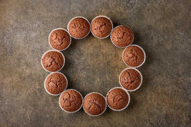 Cupcakes de chocolate caseiros dispostos em forma de círculo na superfície de madeira, copie o espaço, topo