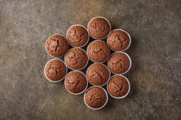 Cupcakes de chocolate caseiros dispostos em forma de favo de mel na superfície de madeira, copie espaço, topo