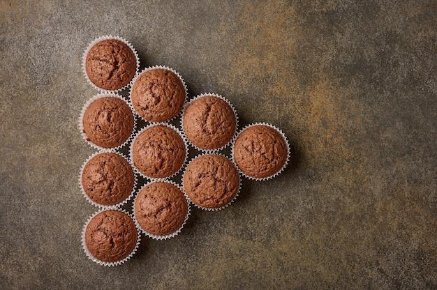Cupcakes de chocolate caseiros dispostos em forma de triângulo em uma superfície de madeira, copie o espaço, topo