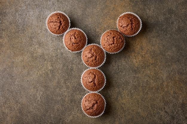 Cupcakes de chocolate caseiros dispostos na forma da letra y em uma superfície de madeira, copie o espaço, topo