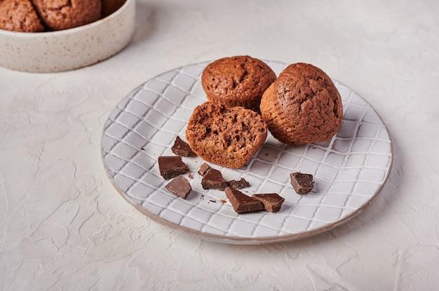 Cupcakes de chocolate caseiros e pedaços de chocolate em placa texturizada no topo de fundo claro de madeira
