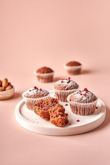 Cupcakes de chocolate caseiros em formas de papel manteiga e pedaços deles na placa de luz em pó rosa