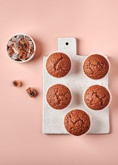 Cupcakes de chocolate caseiros em formas de papel manteiga em uma tábua de cortar em um fundo rosa pulverulento