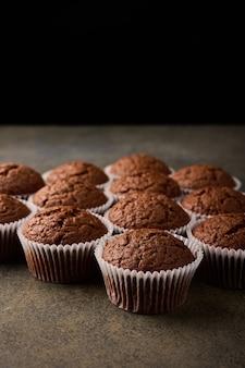 Cupcakes de chocolate caseiros em formas de papel manteiga na superfície de madeira, foco seletivo, close-up
