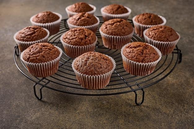 Cupcakes de chocolate caseiros em uma grade de suporte em superfície de madeira, close-up, foco seletivo