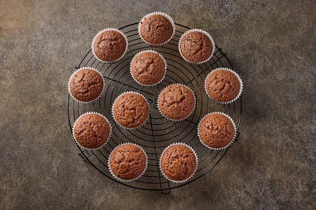 Cupcakes de chocolate caseiros em uma grade de suporte em superfície de madeira, vista superior