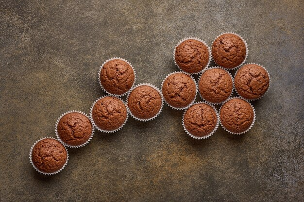 Cupcakes de chocolate caseiros são forrados com formas de flores, copie o espaço, vista de cima