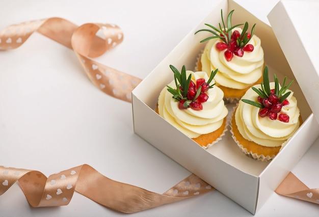Cupcakes de dia dos namorados com baunilha em uma caixa em um fundo branco com fita