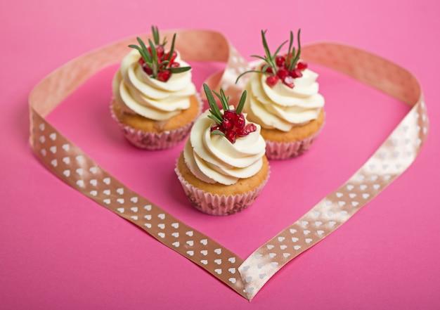 Cupcakes de dia dos namorados com cobertura de baunilha e decorado com coração de fita.