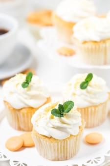 Cupcakes de limão decorados creme de queijo e lascas de chocolate laranja