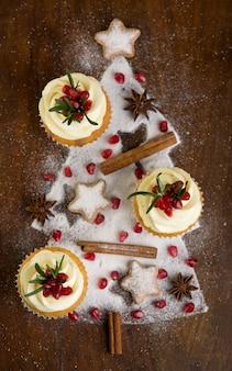 Cupcakes de natal com cobertura de baunilha, cranberries e alecrim em fundo de madeira. foco seletivo