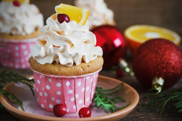 Cupcakes de natal com cobertura de chantilly e cranberries, laranja. sobremesa de comida festiva.