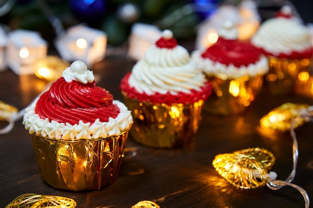 Cupcakes de natal vermelhos e brancos em um fundo de guirlandas brilhantes