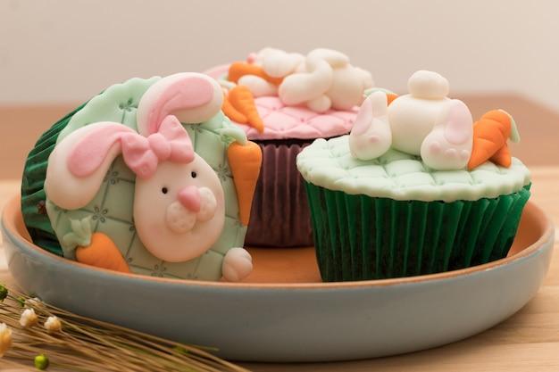 Cupcakes de páscoa deliciosos na placa rústica e fundo de madeira