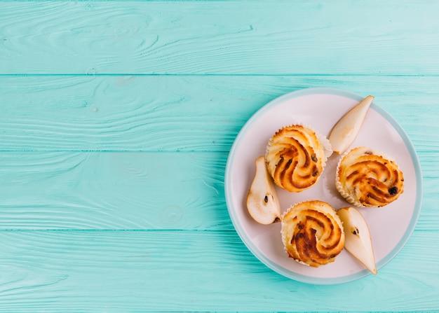 Cupcakes de pêra doce na chapa branca sobre o pano de fundo turquesa de madeira