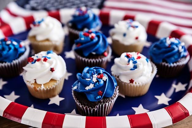 Cupcakes de quatro de julho em um prato de papel com uma bandeira americana