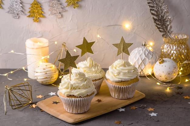 Cupcakes de sobremesa elegante de natal com creme e estrelas douradas