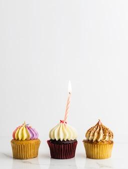 Cupcakes de variedade com vela festa de aniversário no fundo branco, conceito de aniversário