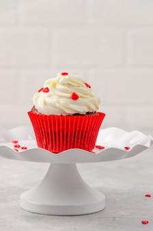 Cupcakes de veludo vermelho com cobertura de cream cheese são decorados para o dia dos namorados