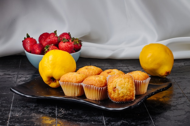 Cupcakes de vista frontal em um prato com marmelo e morangos em uma tigela