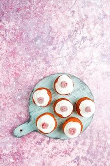 Cupcakes decorados chantilly e framboesas congeladas.