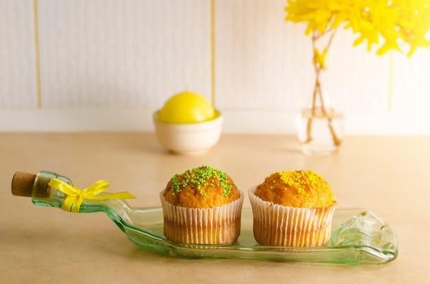 Cupcakes decorados com chuviscos em um prato feito de garrafa em uma mesa de kithchen