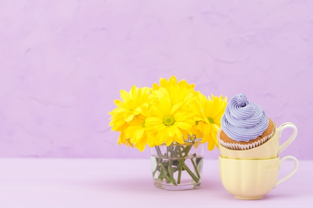 Cupcakes decorados com creme violeta e buquê de crisântemos amarelos